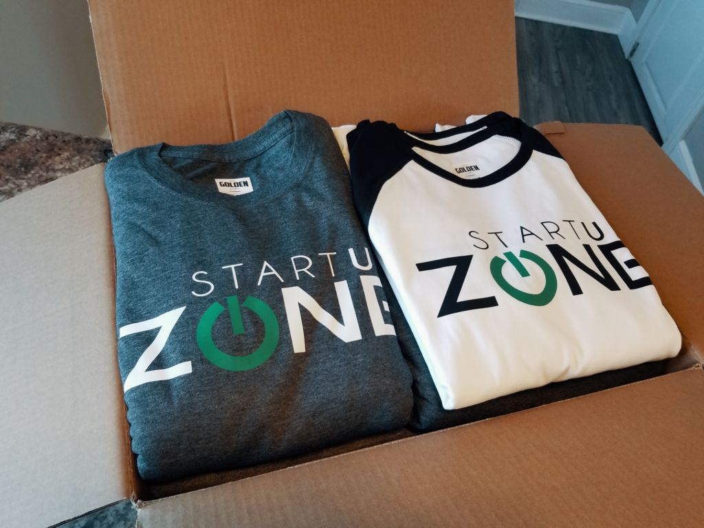 a box of golden custom shirts that have just been printed with the start up zone logo