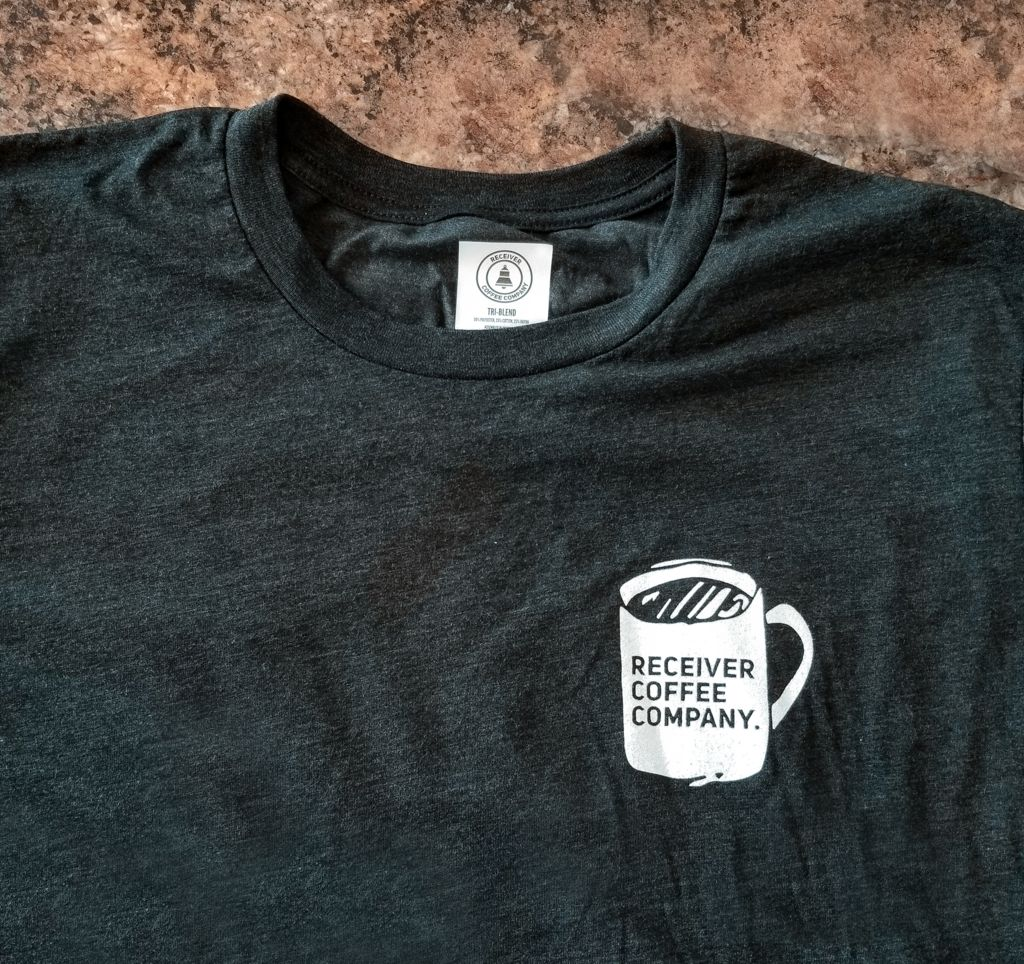 a heather black tri-blend shirt from golden custom that has a coffee mug logo that says receiver coffee company