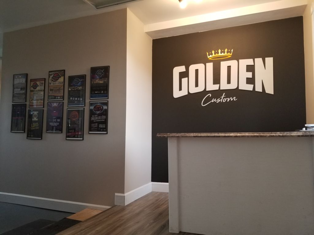 golden custom clothing store lobby with the logo and a front counter